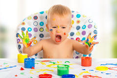 Happy child draws with colored paints hands Stock Photography