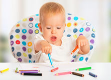 Happy child draws with colored pencils crayons. Happy baby child draws with colored pencils crayons Stock Photo