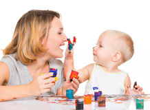 Happy child draws on the face of his mother. Stock Photos