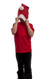 Happy child draws over his face his Santa hat to hide Royalty Free Stock Images