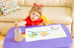 The happy child draws paints. The happy girl draws paints a picture stock image