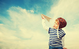 Happy child dreams of becoming pilot aviator and plays with plan Stock Photos