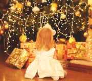 Happy child dreams near christmas tree with gifts boxes home Stock Image