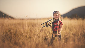Happy child dreams of traveling and playing with an airplane pil Royalty Free Stock Photo