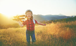 Happy child dreams of traveling and playing with an airplane pil Royalty Free Stock Images
