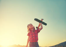 Happy child dreams of traveling and playing with an airplane pil Royalty Free Stock Image