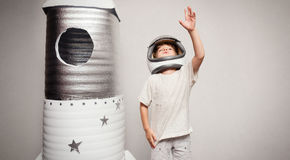 Happy child dressed in an astronaut costume playing with hand ma Royalty Free Stock Photos