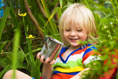 Happy child drinking milk in garden. Outdoor portrait of a cute chld drinking milk in the garden Royalty Free Stock Images