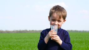Happy child drinks fruit juice from a glass in nature. Healthy and proper nutrition of children. Environmentally