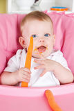 Happy child eating carrot Royalty Free Stock Image