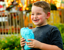 Happy child eating cotton candy Stock Photos