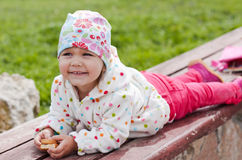 Happy child eating crackers lying on a bench. On a background of green grass in spring royalty free stock images