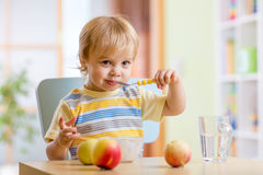 Happy child eating food cheese with fruits at home Royalty Free Stock Images