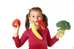 Happy child eating healthy food fruits vegetables. Isolated on white background Royalty Free Stock Photo