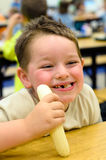 Happy child eating healthy lunch in school cafeteria Stock Images
