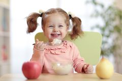 Happy baby eating porridge with spoon Royalty Free Stock Images