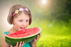Happy child eating watermelon in the garden Stock Images