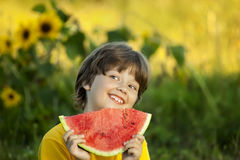 Happy child eating watermelon in garden. Boy with fruit outdoors Royalty Free Stock Photos
