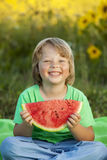 Happy child eating watermelon in garden. Boy with fruit outdoors Stock Photo