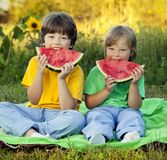 Happy child eating watermelon in garden. Two boys with fruit in. Happy child eating watermelon in the garden. Two boys with fruit in park royalty free stock photo