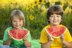 Happy child eating watermelon in garden. Two boys with fruit in Royalty Free Stock Photos