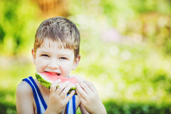 Happy child eating watermelon in summer park. Royalty Free Stock Image