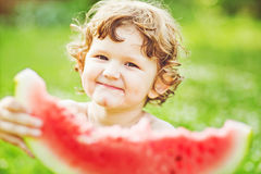 Happy child eating watermelon in summer park. Instagram filter. Royalty Free Stock Photography