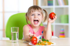 Happy child eats dinner and shows tomatoes royalty free stock photography