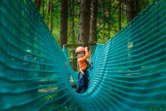 Happy child enjoying in a climbing adventure park Stock Photo