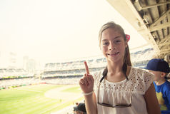 Happy Child enjoying a day at a baseball game. A smiling happy little girl showing a No. 1 finger sign while watching a professional baseball game. She is Royalty Free Stock Photo