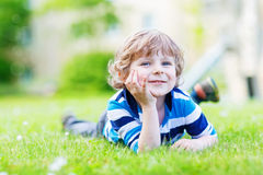 Happy child enjoying on grass field and dreaming Royalty Free Stock Photography