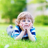 Happy child enjoying on grass field and dreaming Royalty Free Stock Image