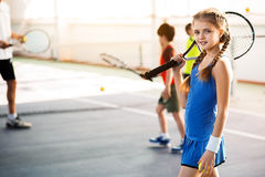 Happy child enjoying tennis game with her group Royalty Free Stock Photos