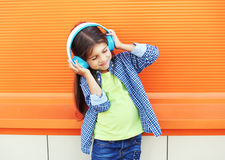 Happy child enjoys listens to music in headphones over colorful orange Stock Images