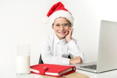 Happy child is expressing gladness. Merry christmas concept. Portrait of joyful girl wearing red hat of santa claus and eyeglasses. She is leaning elbow on desk stock photo