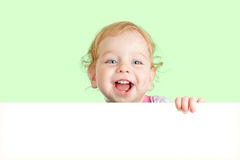 Happy child face behind blank advertising banner royalty free stock image