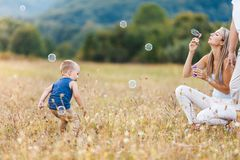 Happy child with family having a great time blowing bubbles stock photography