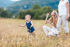 Happy child with family having a great time blowing bubbles royalty free stock image