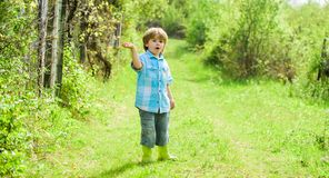 Happy child farmer in rubber boots, spring. human and nature. earth day. Eco life. summer activity. small kid gardener. Walking in forest. farming and stock images