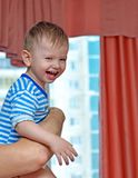 Happy child on the father`s hands near a window Royalty Free Stock Photos