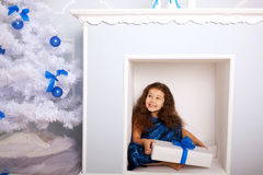 Happy child in fireplace waiting for gifts. Stock Photo