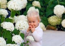 Happy child among flowers Stock Photo