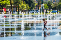 Happy child among the fountains Royalty Free Stock Image