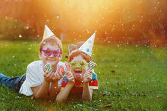 Happy child friend in carnival party, lying on a green grass in Stock Image