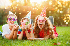 Happy child friend in carnival party, lying on a green grass in Stock Images