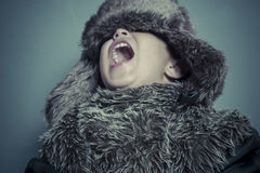 Happy child with fur hat and winter coat, cold concept and stor royalty free stock photography