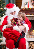 Happy child with gift sitting on Santa Claus lap Stock Photo