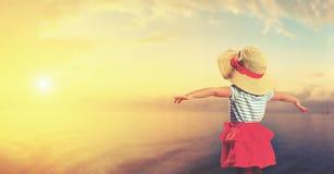Happy child girl admiring sunset on beach Royalty Free Stock Photos