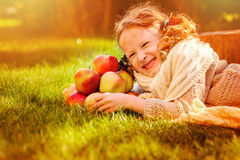 Happy child girl with apples in autumn sunny garden Stock Photography