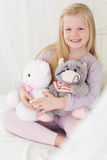 Happy child girl in the bed with her soft toys Royalty Free Stock Photos
